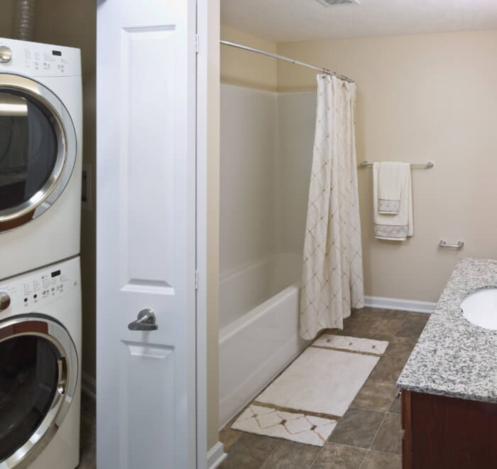 Bathroom with washer and dryer unit in closet